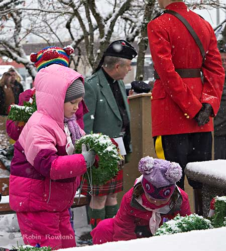 Girl lays wreath Remembrance Day 2012