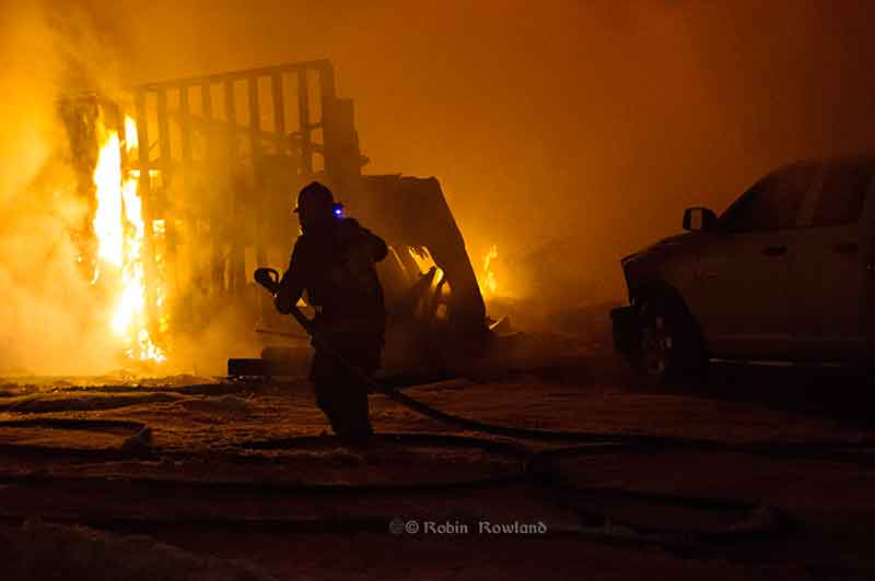 A Kitimat firefighter battles flames on Whitesley Street. March 2. 2013 (Robin Rowland)