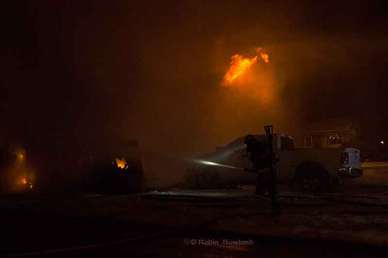 A Kitimat firefighter sprays water on the stubborn fire on the garage on Whittlesey Street. (Robin Rowland)