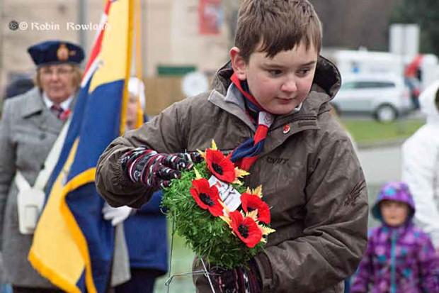 Boy lays wreath