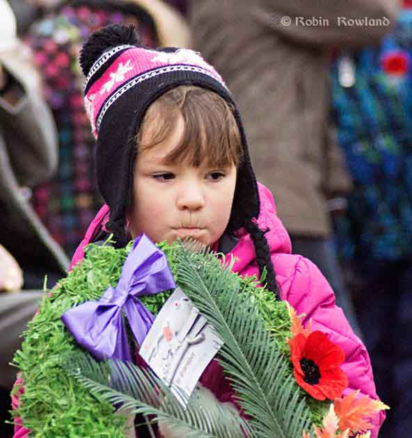 Girl lays wreath at the cenotaph