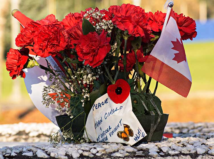 A bouquet of carnations with two maple leaf flags honouring Cpl. Nathan Cirillo and Warrant Officer Patrice Vincent was left on the Kitimat Cenotaph prior to Tuesday's Remembrance Day ceremony. (Robin Rowland)