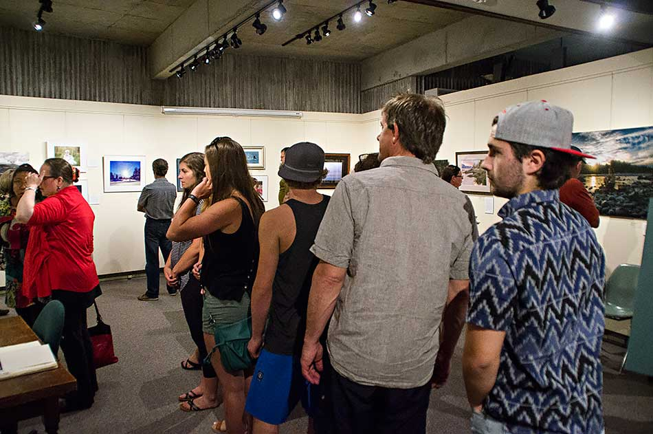 Visitors line up to see the photo s at the opening of the North West Photo Fest exhibit at the Kitimat Museum & Archives, August 5, 2016. (Robin Rowland)