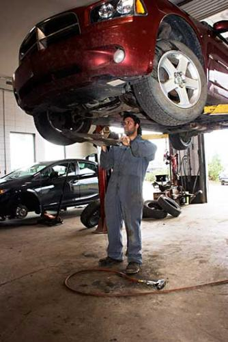 Apprentice Jonah Preston works on a car at Kalum Tire Service in Terrace. BC,  June 19 2014