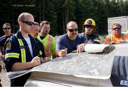 Employees of Oviatt Construction are briefed by Kitimat Fire & Rescue before building a firebreak during a forest fire in Kitimat, July 7, 2014.