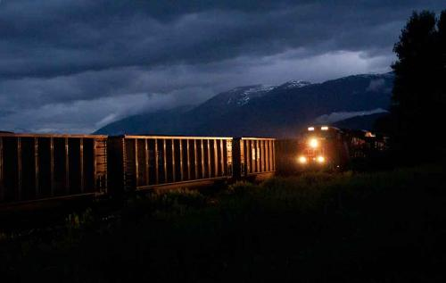 An  intermodal container train enters the CN yards at Terrace, BC, passing a westbound coal train,  during a rainstorm, July 18, 2011. (Robin Rowland)