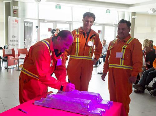 Kitimat mayor Phil Germuth signs the new ingot as Phil Newsome, Bechtel and Michel Charron, Rio Tinto, watch during the Kitimat Modernization First Metal Ceremony, July 7, 2015.